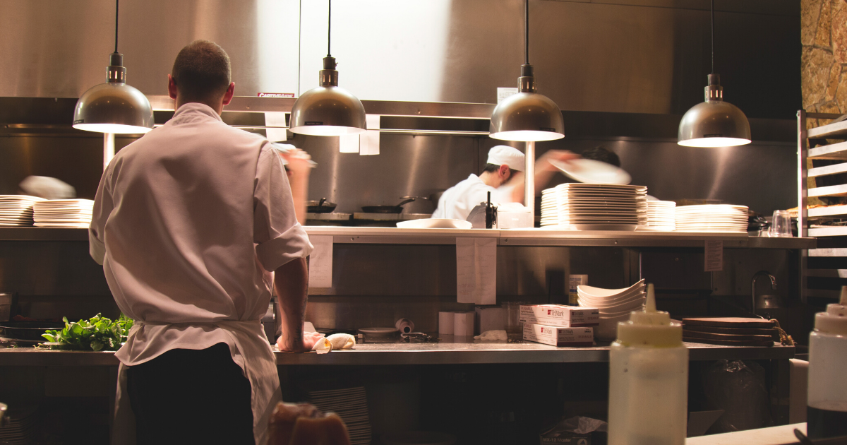 Cooks prepare food in the kitchen of a fine dining restaurant